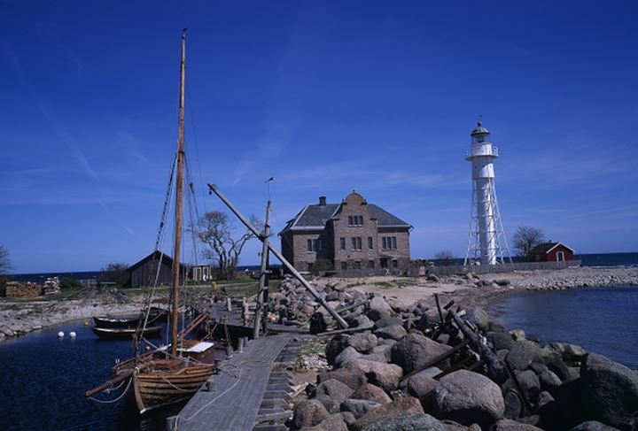 A white lighthouse with buildings and boats