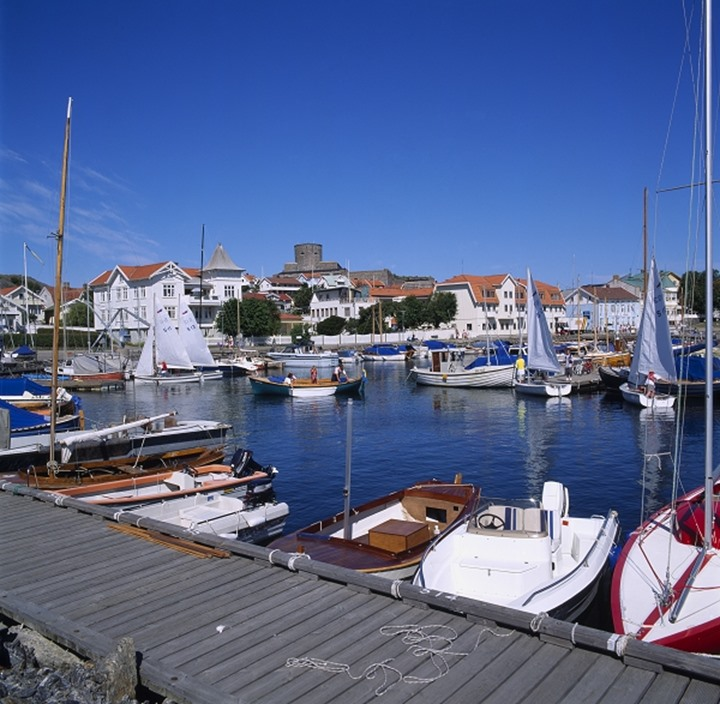 Boats in the harbour with houses and blue sky