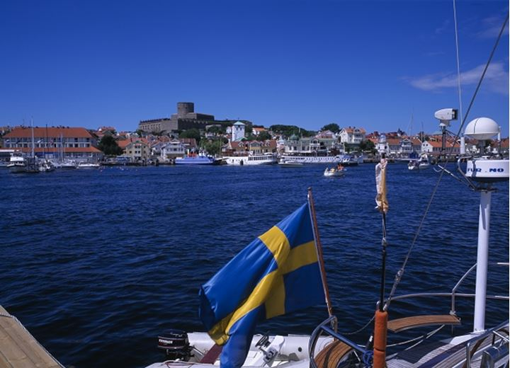 Homes with boats and Swedish flag in the foreground