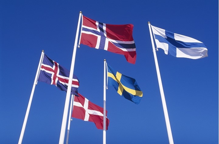 Low angle view of the flags of the Nordic countries waving against blue sky