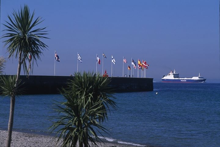 Ship moving in the sea with flags on the harbour