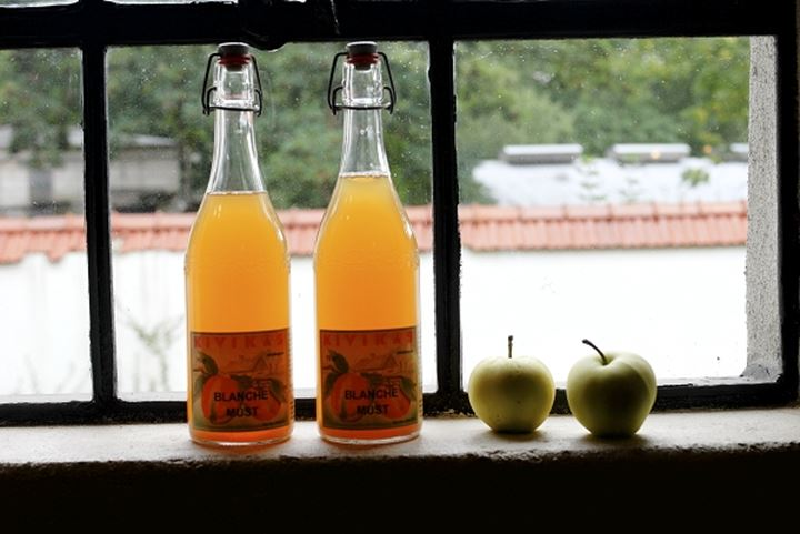 Juice bottles and apples on a windowsill