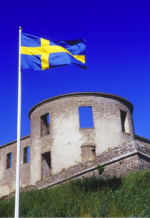 Swedish flag waving by a building against blue sky