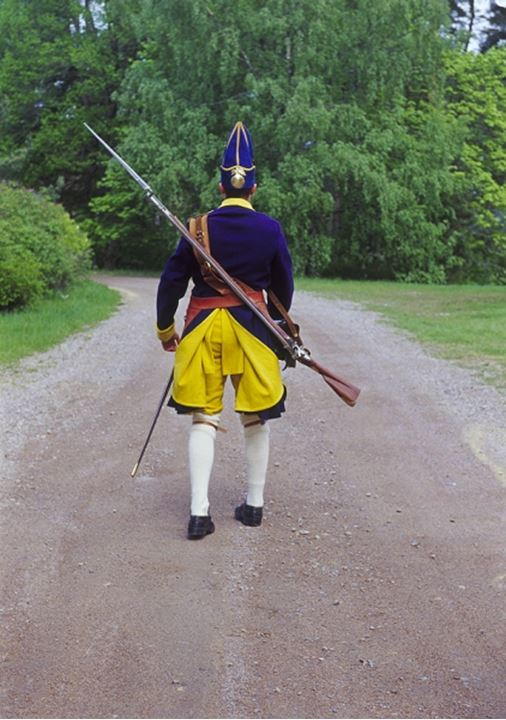 Rear view of an equipped warrior walking on the road whilst wearing costumes