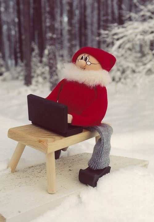 A gnome with a laptop on snow