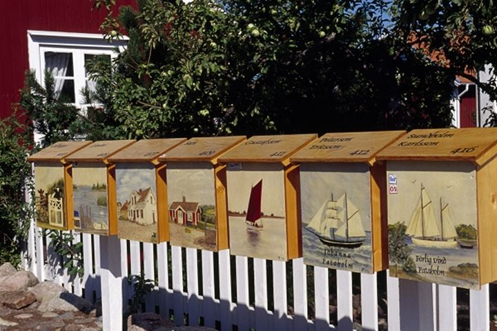 Creatively painted mailboxes with fence and tree