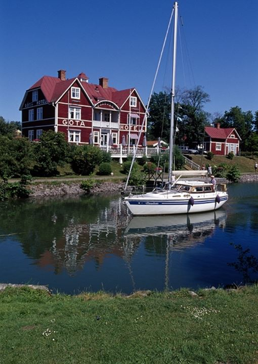 Red house and a sailboat reflecting in the river