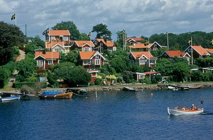 Homes with Swedish flags and boats by the river
