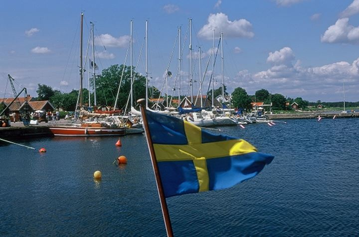 Sailboats anchored with cloudy sky and Swedish flag waving in the foreground