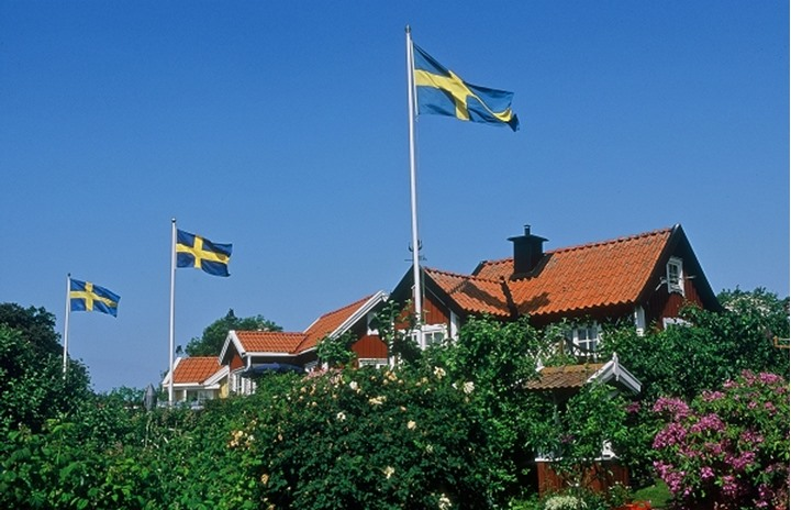 Houses with Swedish flags and blue sky