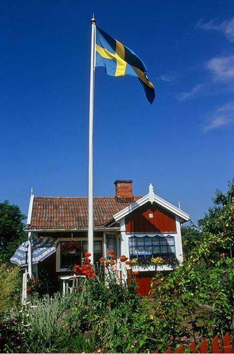 A cottage with chimney and Swedish flag