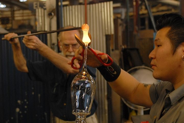 Workers cutting molten glass with scissors
