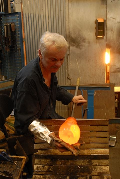 Side view of a man shaping molten glass