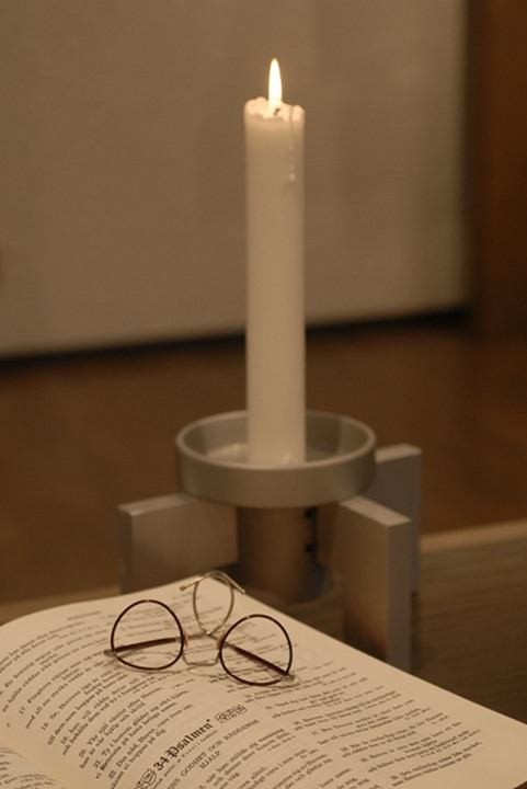 Lit candle by the eyeglasses on a book