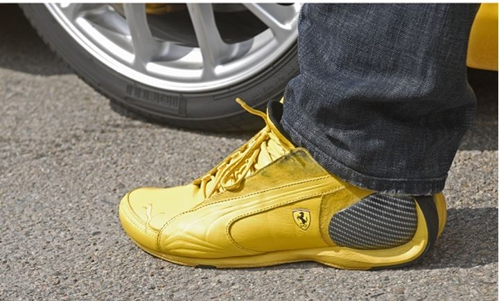 A person wearing yellow shoe with Ferrari Trademark
