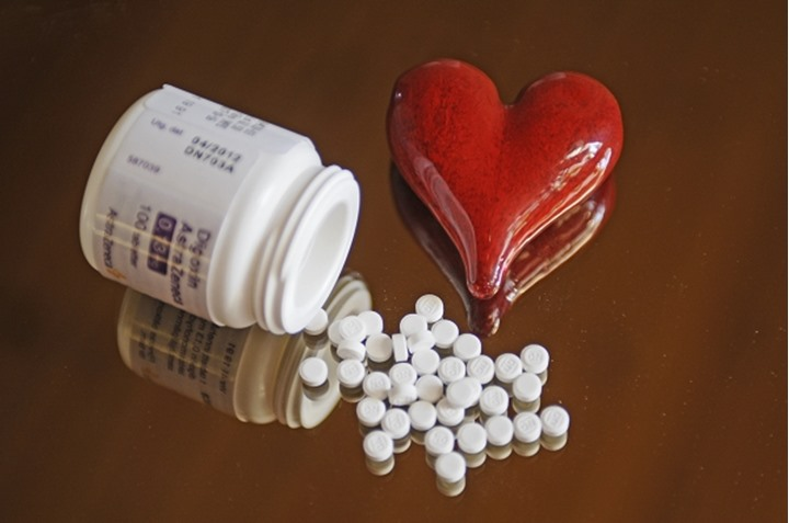Pills on table with red plastic heart