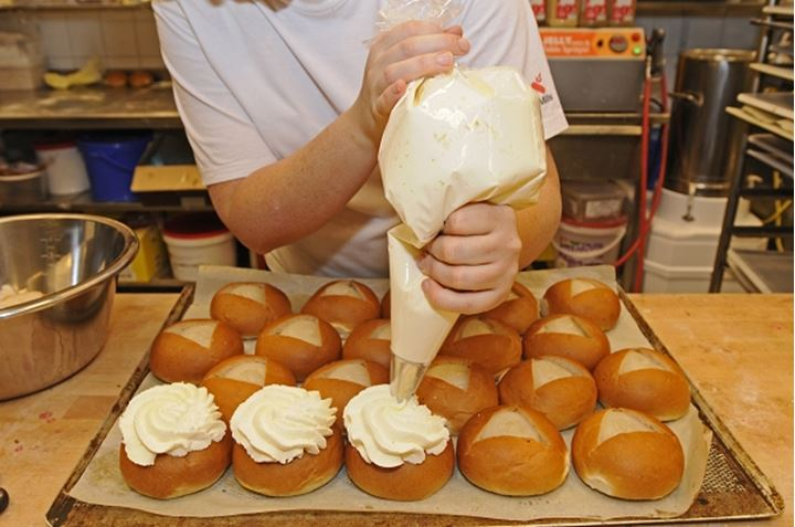 A person applying creame to swedish semlor