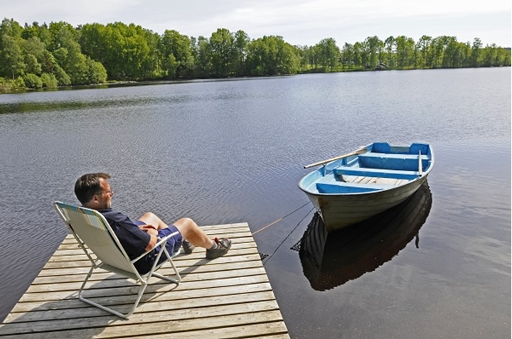 Person sitting on a landing stage near lake, Smaland (Småland), Sweden