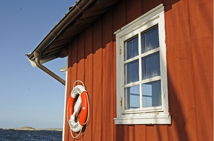 A house by the shore, close-up of roof, life ring and window.  Bohuslan, Sweden.