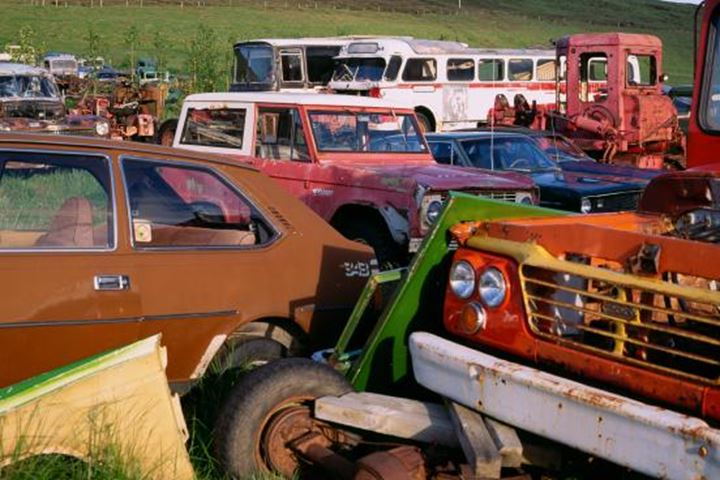 Cars, trucks, and buses sitting in a junkyard