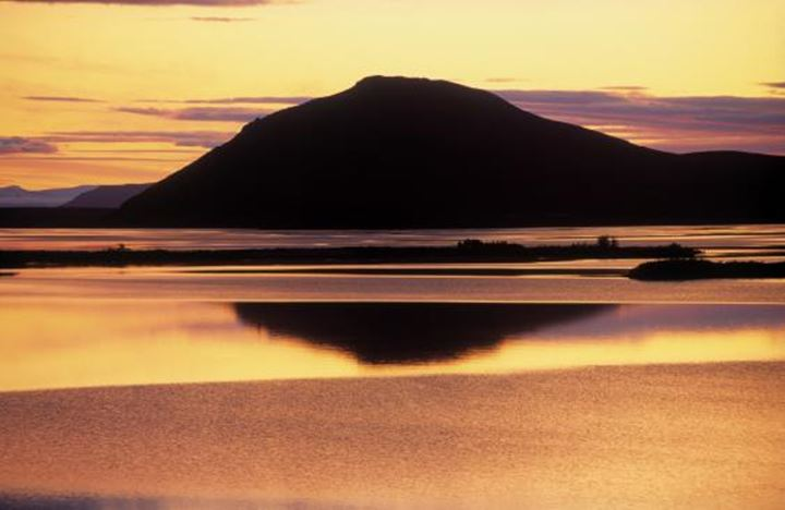 Reflection during sunset of a mountain on the ocean