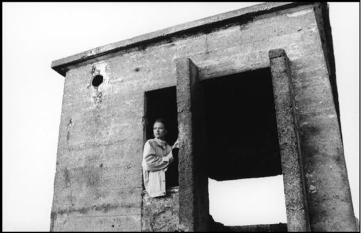 Woman sitting in a window of old stone structure
