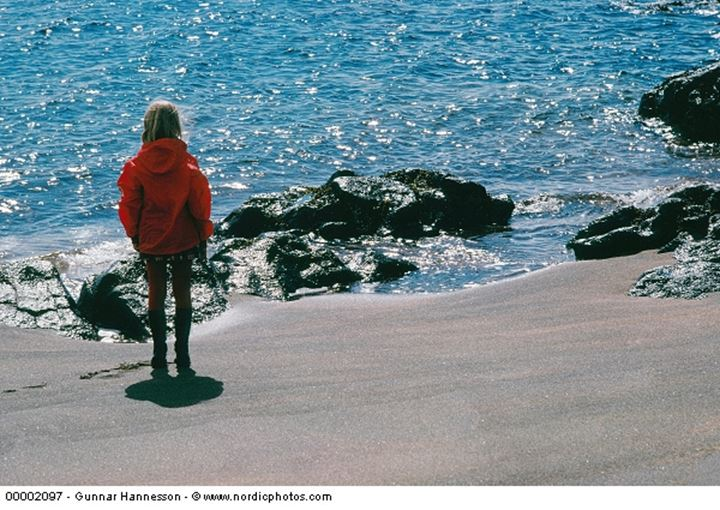 A girl standing by the sea