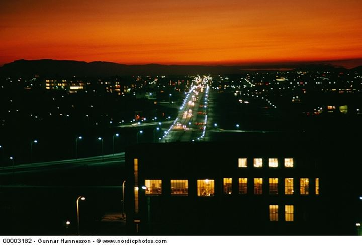 Overlooking Reykjavik at night time, red sky above the city lights.