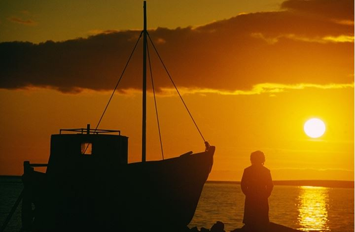 Iceland - Silhouette of a person standing beside a boat at sunset