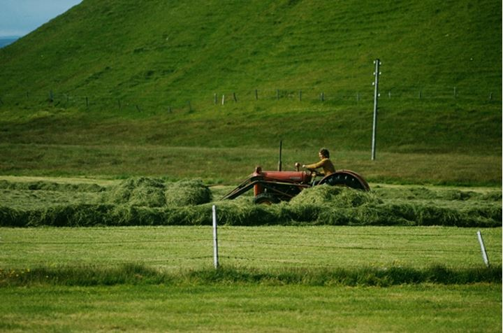 Farmer gathering hay in a field using a tractor