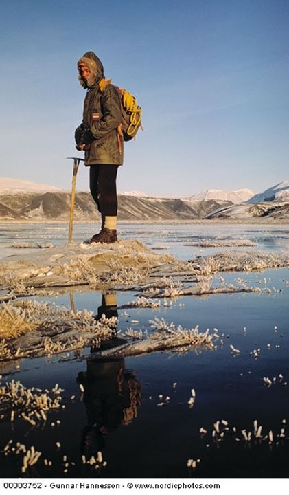 A hiker standing out in a partially frozen river, snow covered mountains behind him.