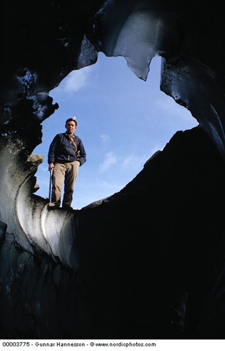 A man standing by the entry of a cave.