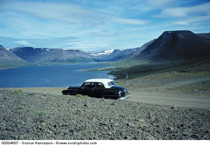 An old car on a dirt road with mountains in the background