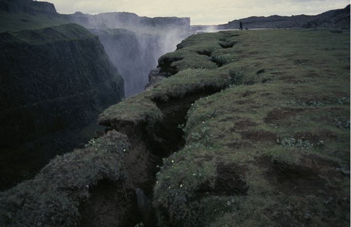 A deep ravine and the spray from Dettifoss ( waterfall )  and a single spectator
