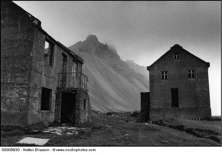 Two large ruined buildings in front of mountain called Vesturhorn