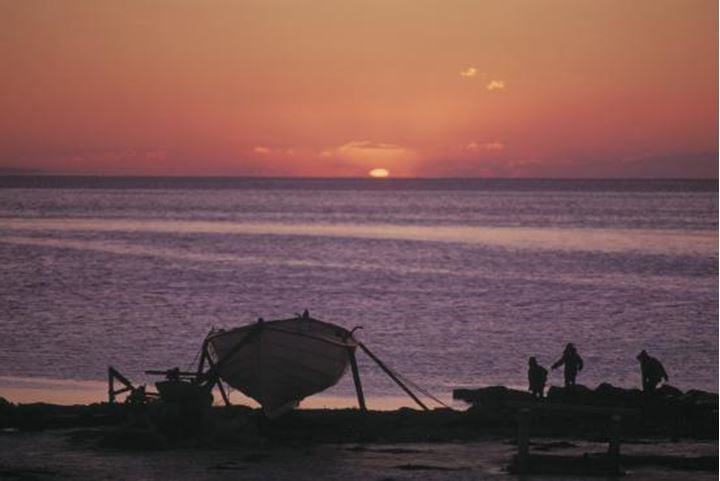 Boat standing in the shore, children playing next to it, sunset.