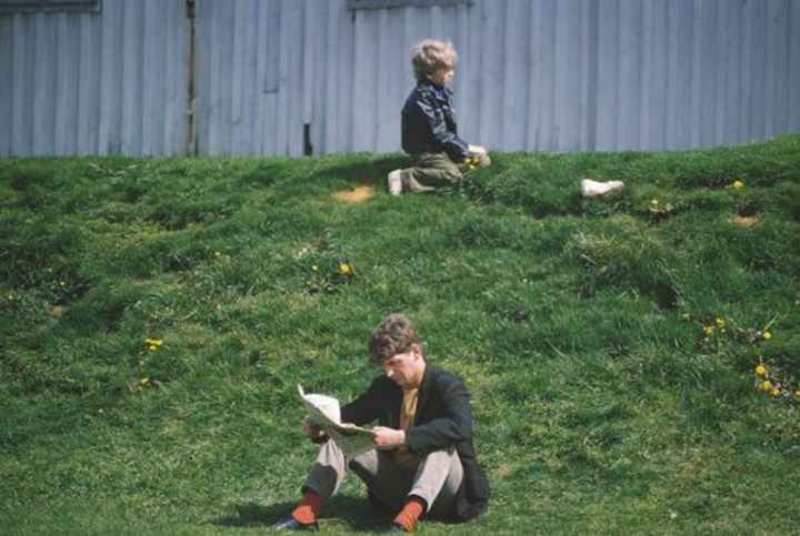 A man and a young boy sitting in the grass