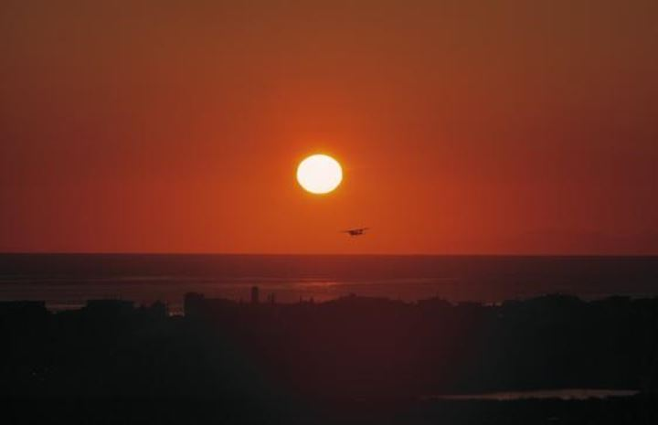 An airplane flying in the sunset