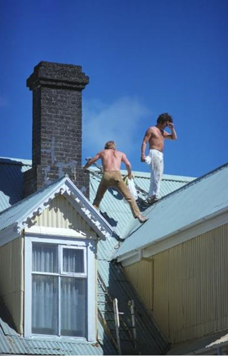 Men working on a roof under the blue sky
