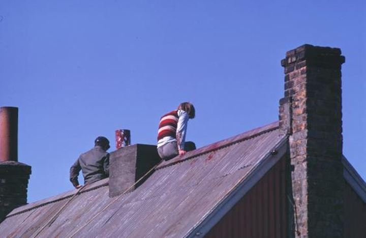 People sitting on rooftops and the blue sky