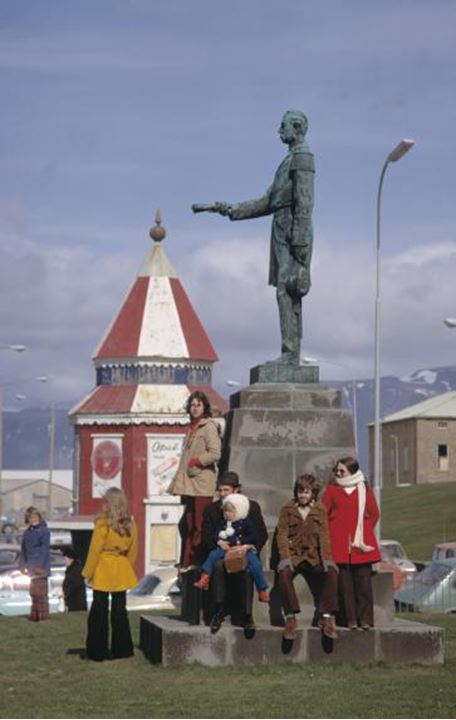 People standing beneath a statue in front of one of the government building in Reykjavik in the´70s.