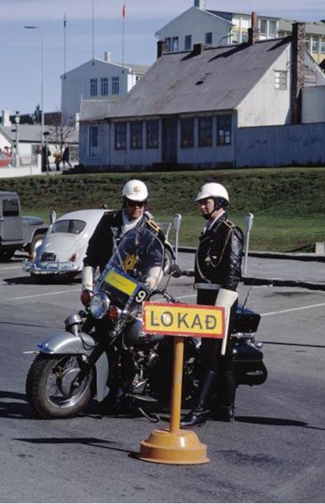 Two police officers by a motorcycle.