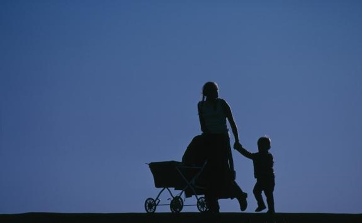 A mother,  pushing a baby carriage and holding her son´s hand.