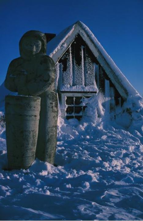 Sculpture of a person churning in front of a timber house covered with snow.