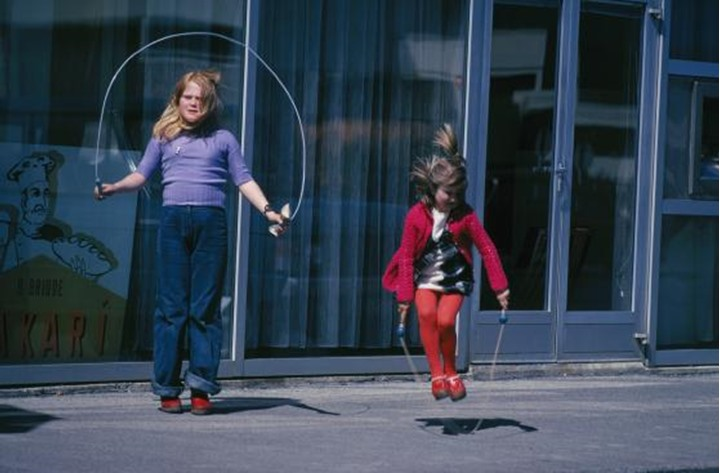Two girls jumping rope on the street