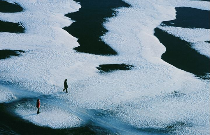 Two people walking over snow covered ground