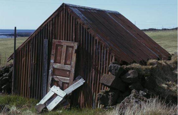An old desolate house with rusty corrugated iron, field in the background.