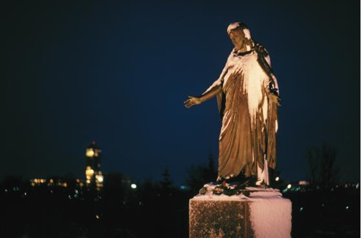 A statue of Jesus Christ with city lights in the background.