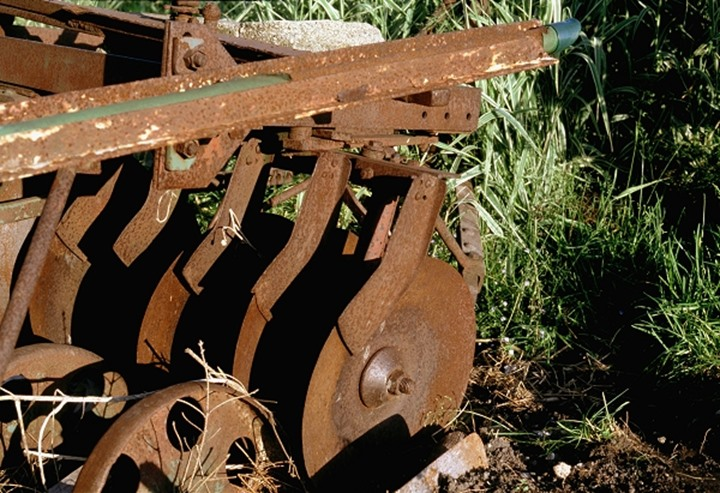 Old and rusty agricultural machine laying on the ground