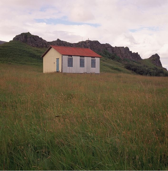 Iceland - Farmhouse in a field with a hill in the background